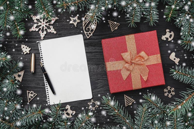 Обои зимних отдыхов на черной предпосылке Красный подарок и деревянные игрушки Ели вокруг Письмо для Санта Клауса с космосом fo стоковые изображения