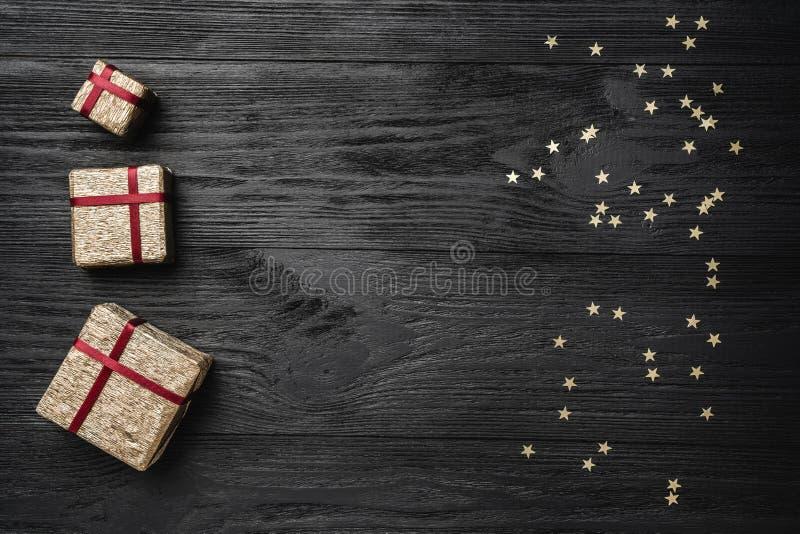 Обои зимних отдыхов на черной предпосылке Подарки и звезды золота Космос для текста Взгляд сверху стоковое изображение rf
