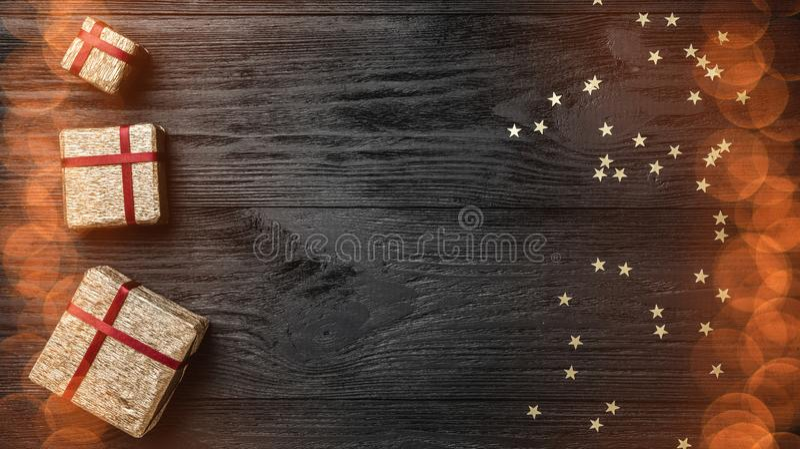 Обои зимних отдыхов на черной предпосылке Подарки и звезды золота Космос для текста Взгляд сверху Поздравительная открытка Xmas стоковые фото