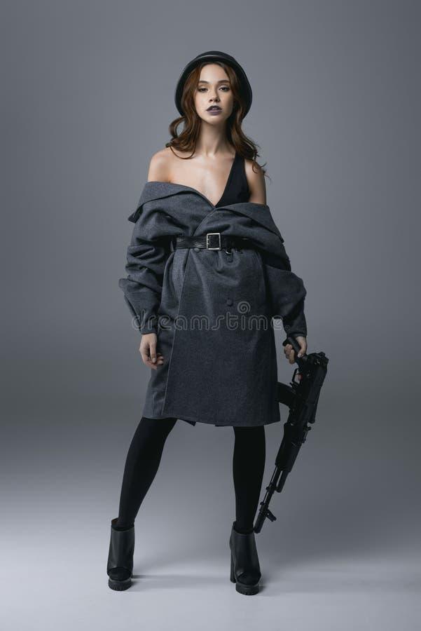 обольстительная красивая женщина представляя в пальто и воинском шлеме с винтовкой, стоковые изображения