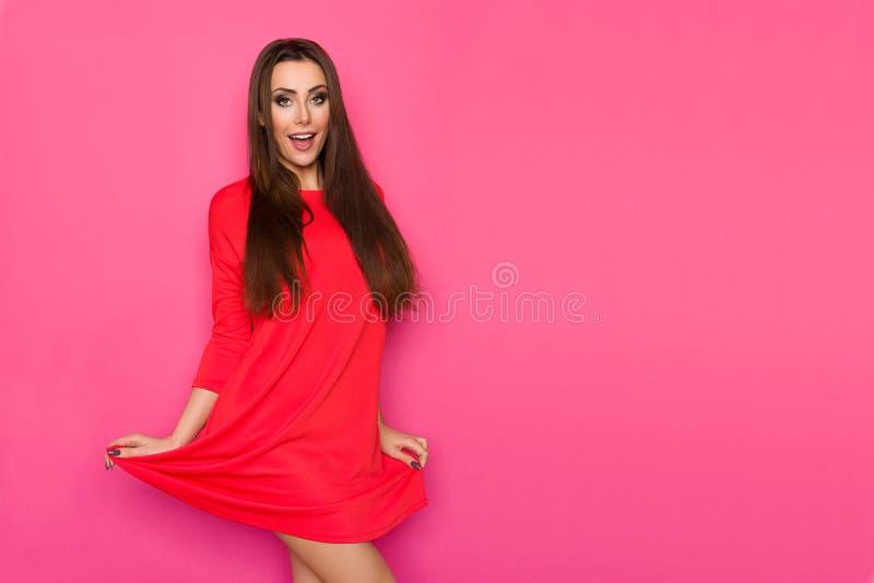 Обольстительная молодая женщина в красном мини платье стоковая фотография