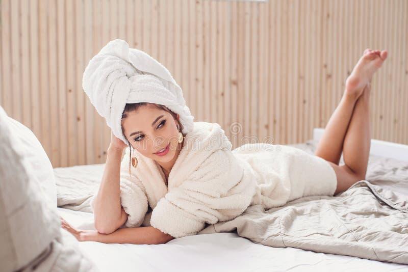 Обольстительная усмехаясь молодая женщина лежа на кровати дома после rpocedures спа утра одетых в белом купальном халате r стоковая фотография rf