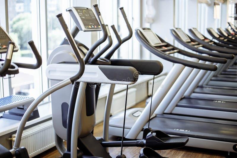 Оборудование и машины на современном фитнес-центре комнаты спортзала стоковые фото
