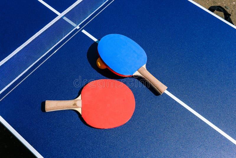 Оборудование настольного тенниса - ракетки, таблица и шарик Игра пингпонга в улице Земное спорт для мероприятий на свежем воздухе стоковое изображение rf
