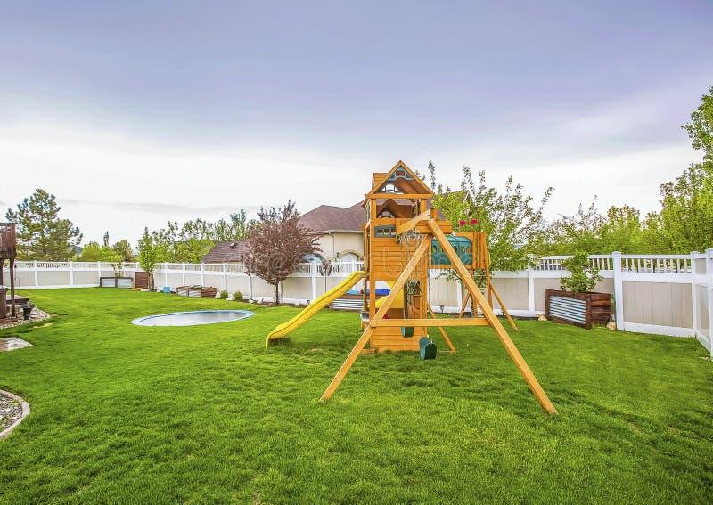 Оборудование спортивной площадки и небольшой бассейн на просторной задворк дома стоковое фото