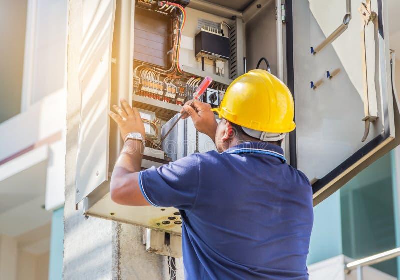 Оборудование электрика привинчивая ремонтируя в коробке автомата защити цепи взрывателя стоковая фотография