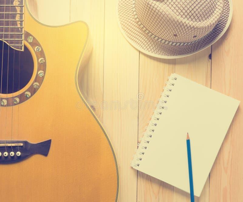 Оборудование музыканта лета, гитара с тетрадью музыки стоковая фотография