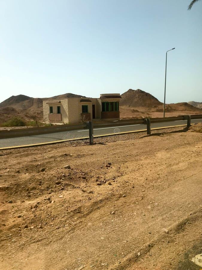 Обочина, дорога с асфальтом в пустыне с песком, бамперы и фонарные столбы, песчанные дюны, холмы, горы и дома в горячем t стоковые изображения rf