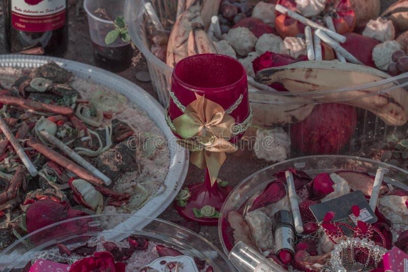Обочина обочины предлагая вероисповедание Candomblé/UmbOffering Candomblé/Umbanda с розами, cigarrettes и licquor стоковая фотография rf