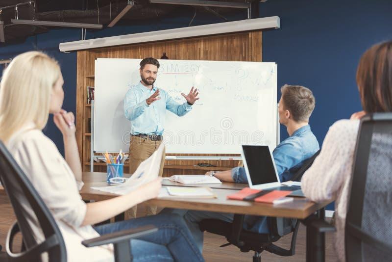 Ободренный бородатые парень и сотрудники проводя семинар работы в офисе стоковые фотографии rf