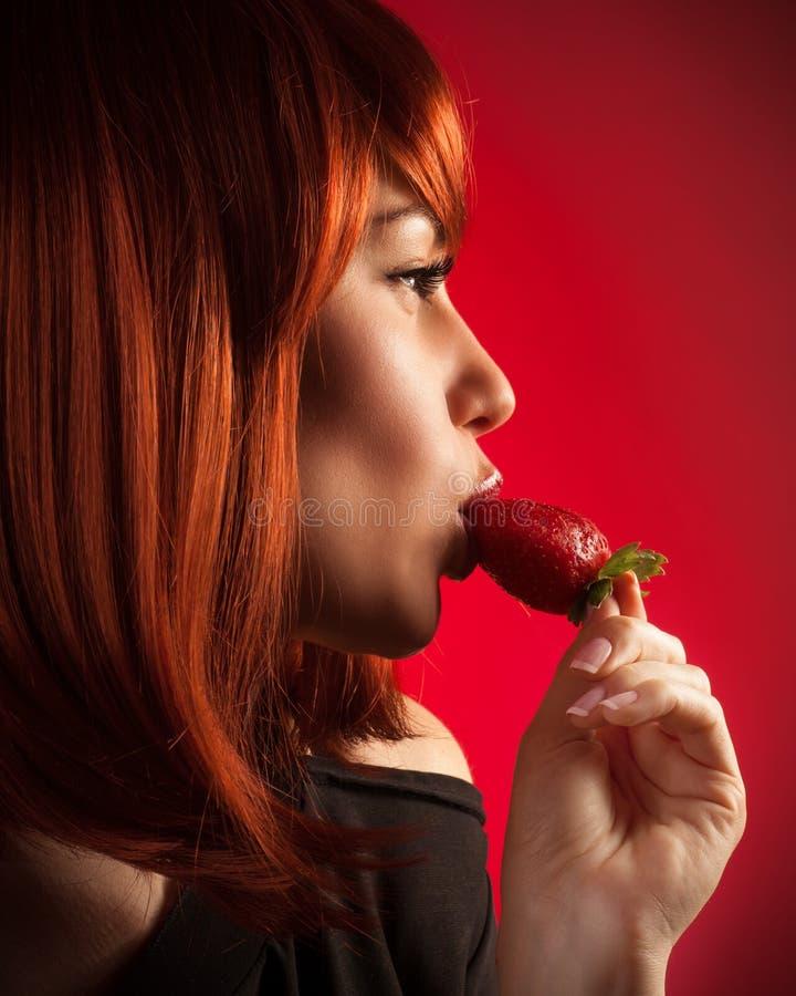 Обольстительная женщина есть клубнику стоковое изображение rf