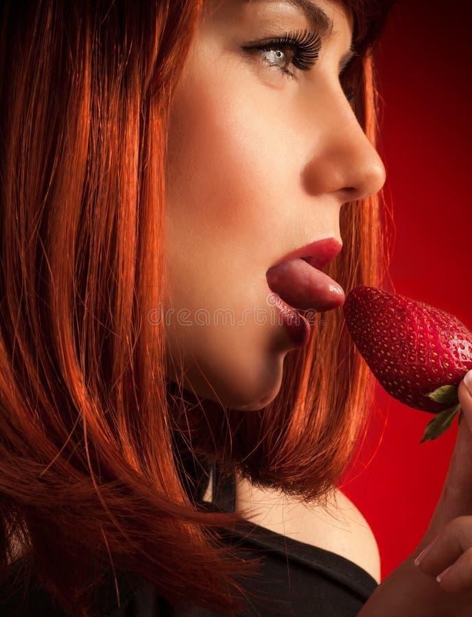 Обольстительная женщина есть клубнику стоковые изображения rf