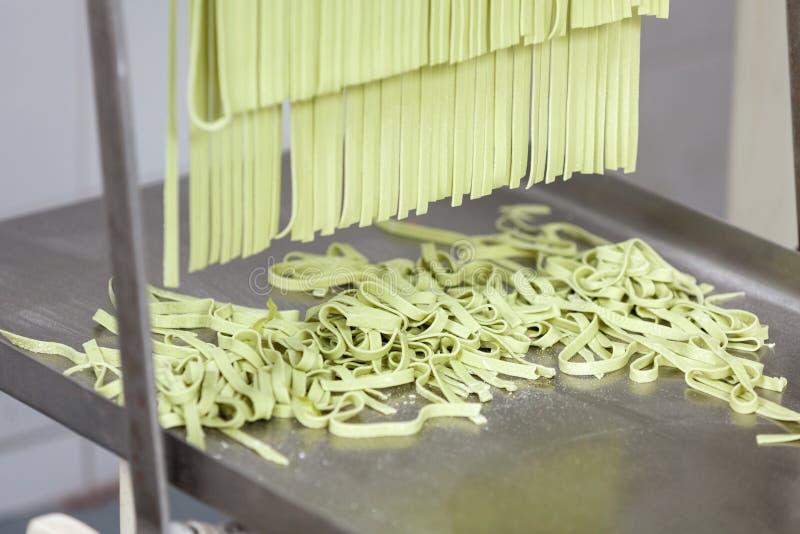 Обрабатываемые макаронные изделия спагетти на подносе машины стоковое изображение rf