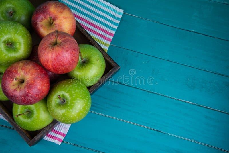 Обрабатывайте землю свежие органические красные и зеленые яблоки на деревянном столе в затире стоковые изображения