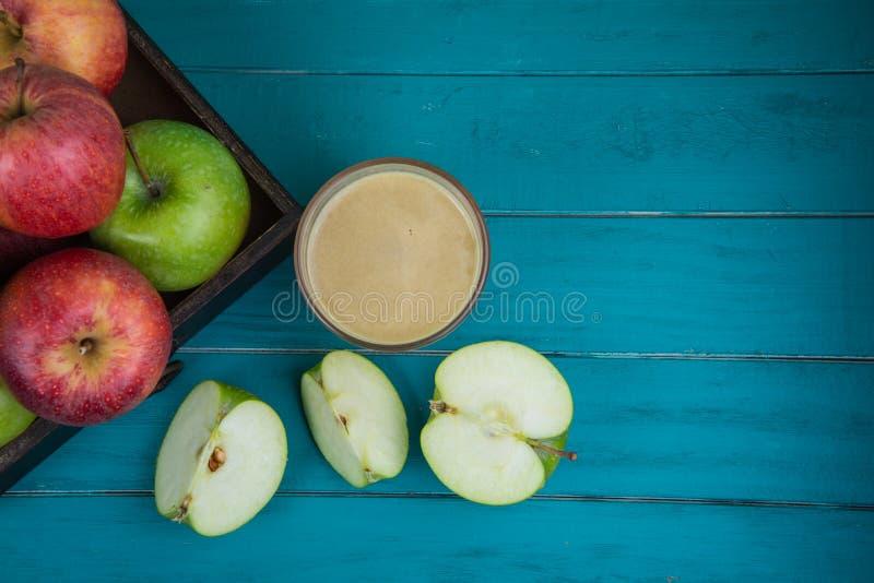 Обрабатывайте землю свежие органические красные и зеленые яблоки отжатый сок в стекле o стоковая фотография
