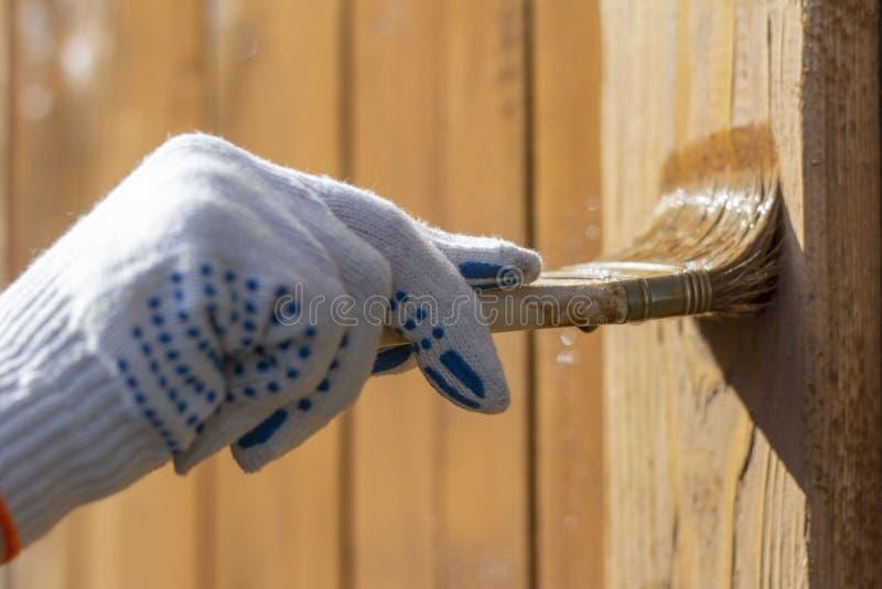 Обработка деревянной стены снаружи Мужская рука в перчатке рисует деревянные стены беседки или веранды щеткой стоковые фото