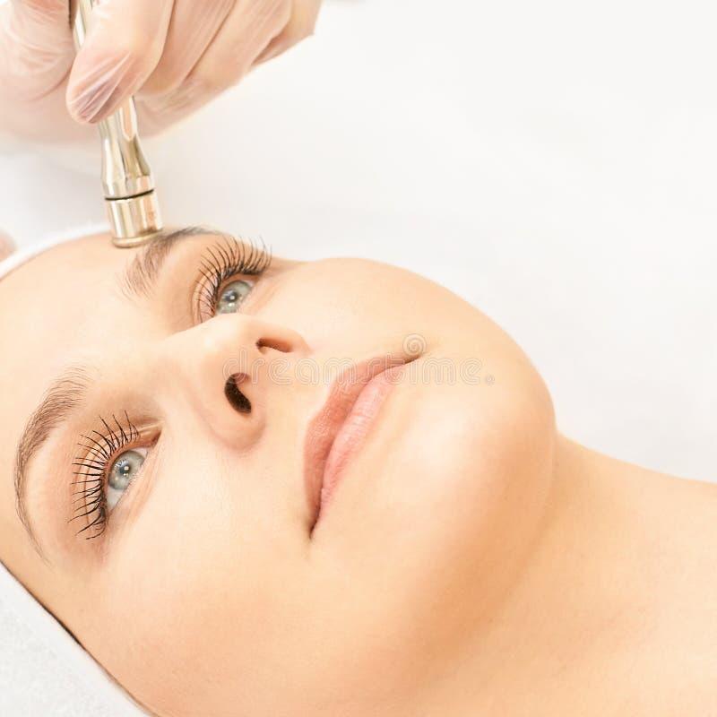 Обработка стороны косметологии Терпеливая маленькая девочка Оборудование салона косметическое Кожа диаманта дерматологии чистая стоковые изображения rf
