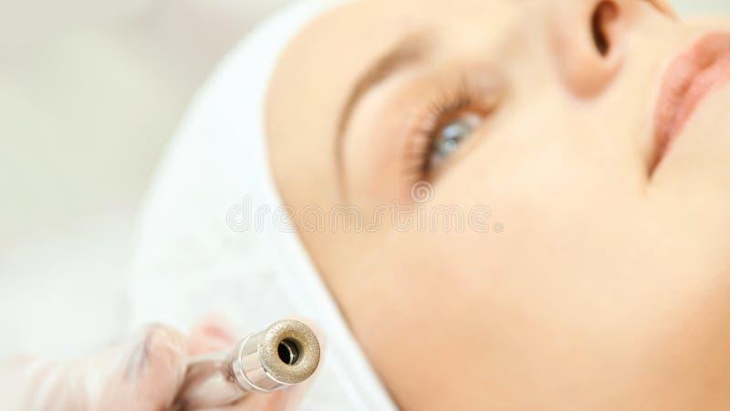 Обработка стороны косметологии Терпеливая маленькая девочка Оборудование салона косметическое Кожа диаманта дерматологии чистая стоковая фотография