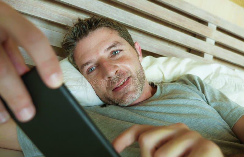 Образа жизни портрет внутри помещения молодой счастливой и привлекательной спальни человека дома используя сеть app средств массо стоковое фото rf