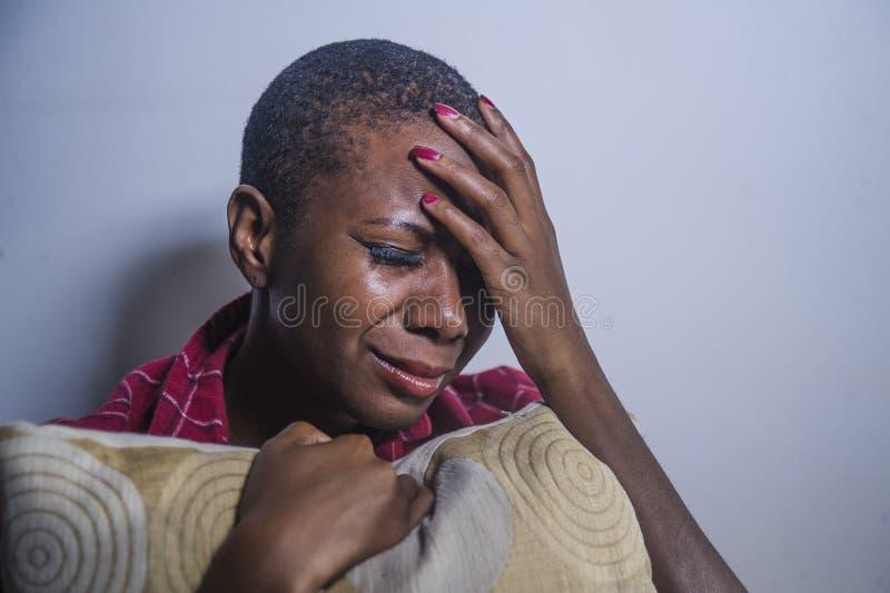 Образа жизни портрет внутри помещения молодой унылой и подавленной черной афро американской женщины сидя дома чувство пола отчаян стоковое изображение rf