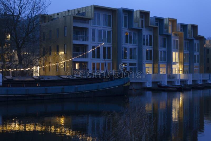 2 образа жизни, старая шлюпка преобразовали к дому рядом с новым комплексом apartemnts, Амстердамом Нидерланды стоковые фотографии rf
