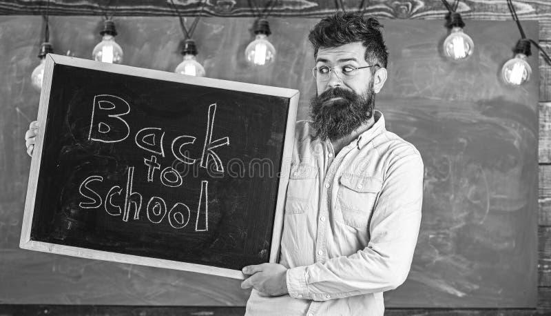 Образование и концепция изучать Человек с бородой и усик на жизнерадостных студентах гостеприимсв стороны, доска на предпосылке стоковые изображения