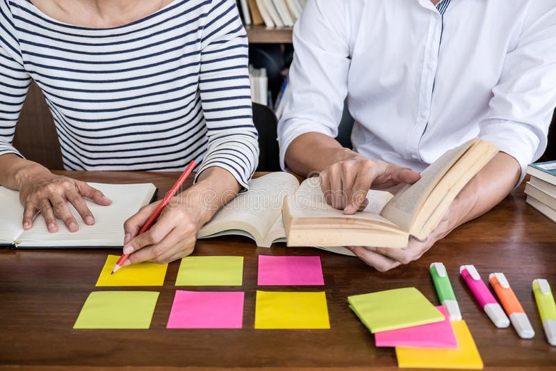 Образование, преподавательство, уча концепцию 2 группы студентов или одноклассников средней школы сидя в библиотеке с делать друг стоковое фото
