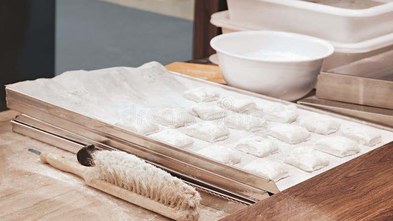 Образование частей теста для pasties пирогов на деревянной floured поверхности стоковые изображения
