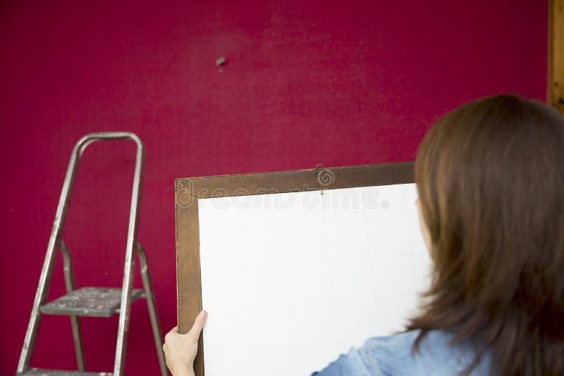 образцы ролика краски Красивые женщины кладя картину к стене i стоковые фотографии rf