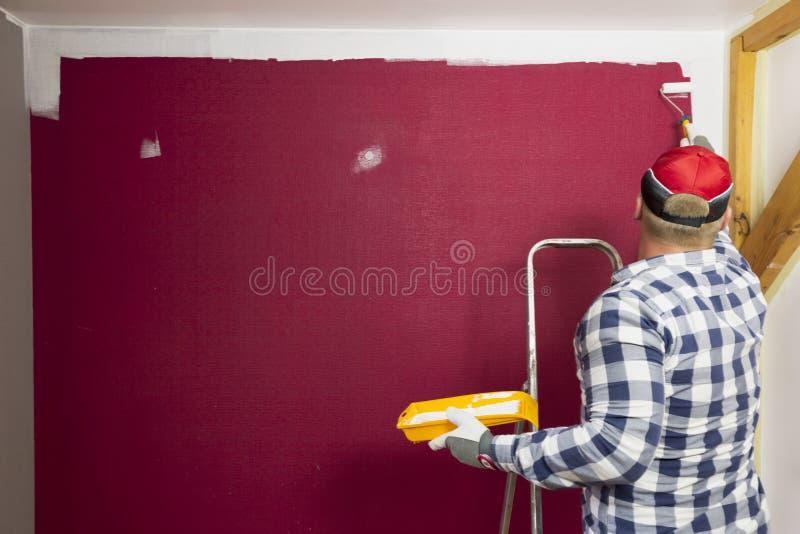 образцы ролика краски Человек в красной шляпе крася комнату с болью стоковые изображения rf