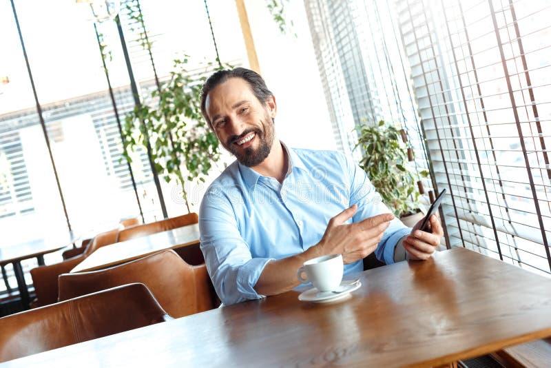 Образ жизни дела Торговец сидя на кафе с видео кофе наблюдая на смартфоне смотря смеяться камеры жизнерадостный стоковые фотографии rf