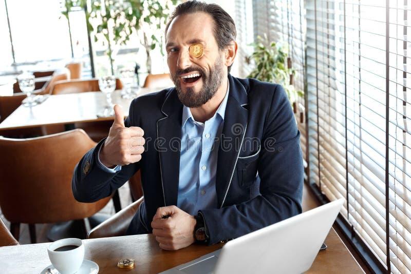 Образ жизни дела Торговец с монеткой cryptocurrency на глазе подмигивая сидеть на кафе с ноутбука и кофе большим пальцем руки вве стоковые фотографии rf