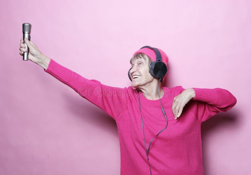 Образ жизни и концепция людей: Музыка смешной пожилой женщины слушая с наушниками и петь с mic над розовой предпосылкой стоковые фото