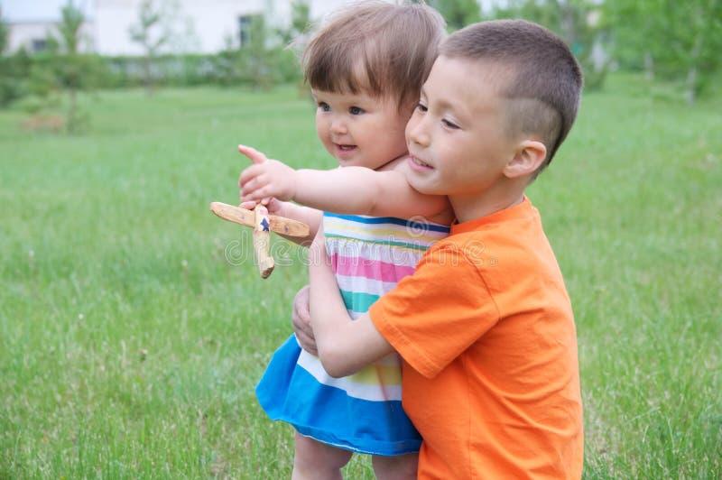 Образ жизни семьи старший брат наблюдая над маленькой сестрой играть детей внешний в парке имея потеху маленькая девочка объятия  стоковое изображение