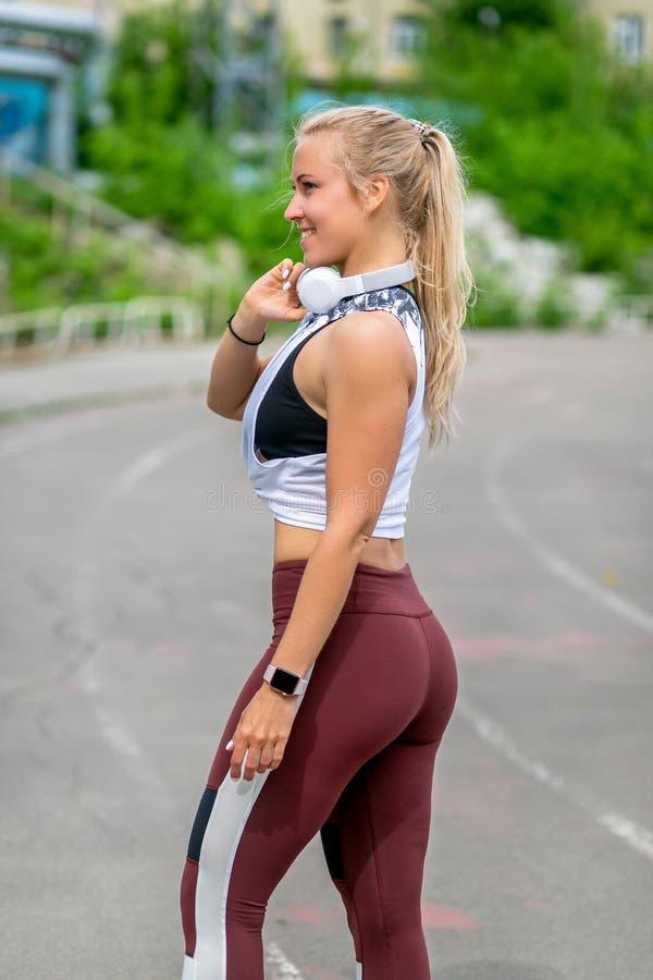 Образ жизни фитнеса 30-год-старая молодая женщина с наушниками представляет во время тренировки r r r стоковые изображения rf