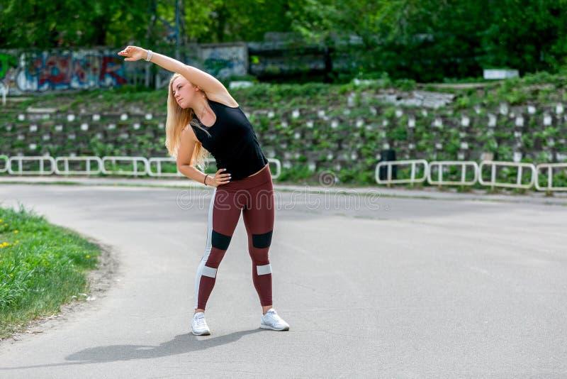 Образ жизни фитнеса Молодая женщина нагревая перед тренируя делая тренировками для того чтобы протянуть ее мышцы и соединения Spo стоковые изображения rf