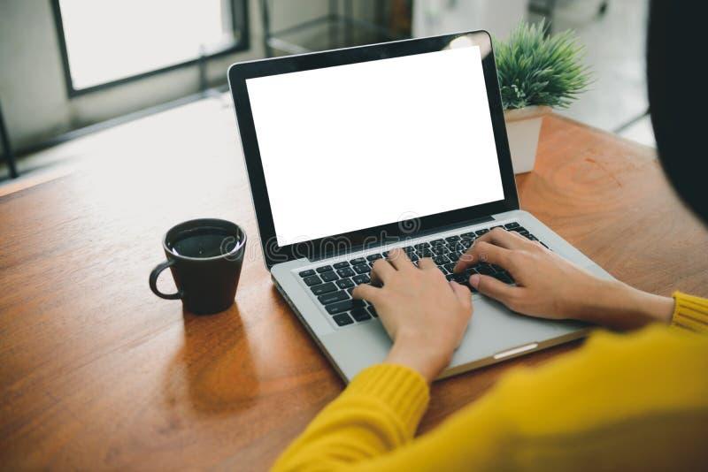 Образ жизни цифров работая вне офиса Женщина вручает печатая портативный компьютер с пустым экраном на таблице в кофейне