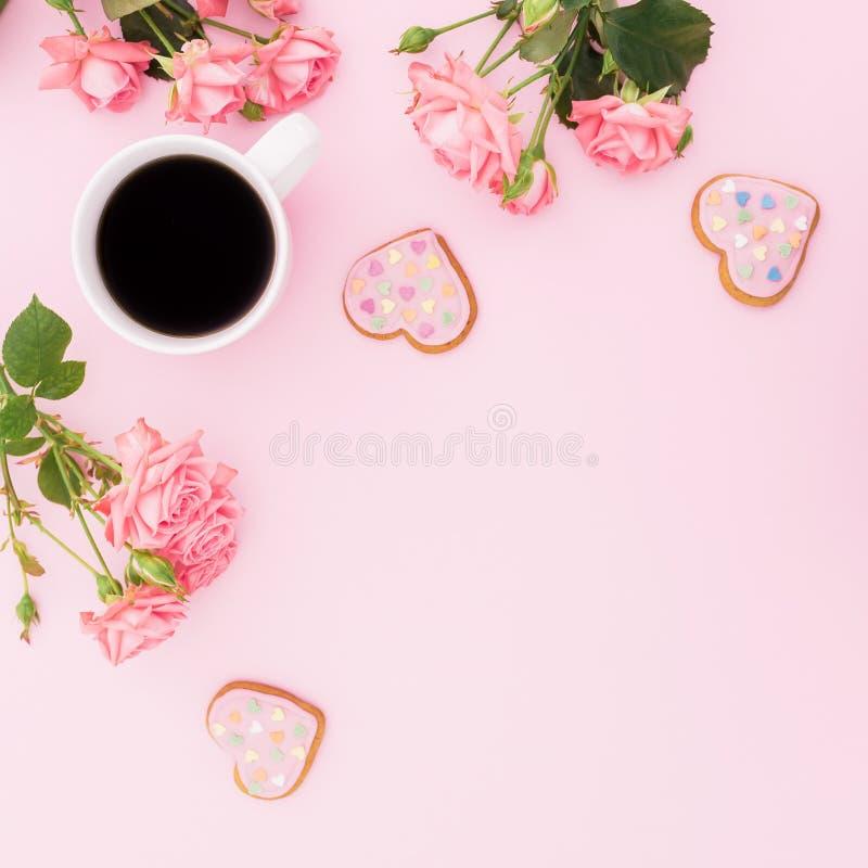 Обрамите состав с цветками роз, сладостными печеньями и чашкой кофе на розовой предпосылке Плоское положение, взгляд сверху стоковая фотография