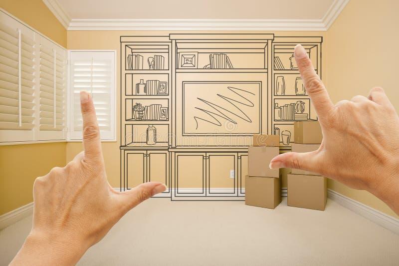 Обрамляя руки в пустой комнате с чертежом полки на стене стоковые фото
