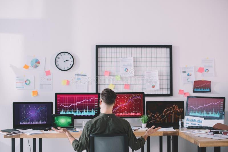 Обратный взгляд на аналитиков данных, сидящих за столом с компьютерами и диаграммами стоковое фото rf