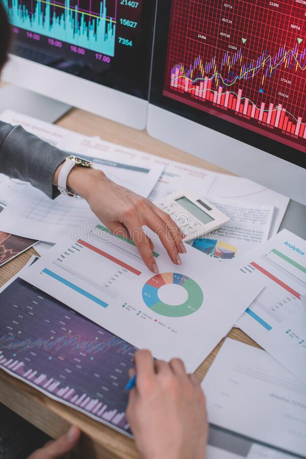 Обрезанное представление аналитиков данных с помощью диаграмм вблизи калькулятора и мониторов компьютеров стоковое изображение rf
