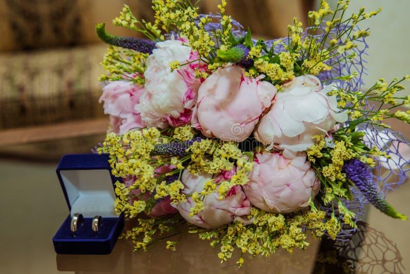 2 обручального кольца в голубой корке на таблице и букете ` s невесты розовых пионов стоковая фотография
