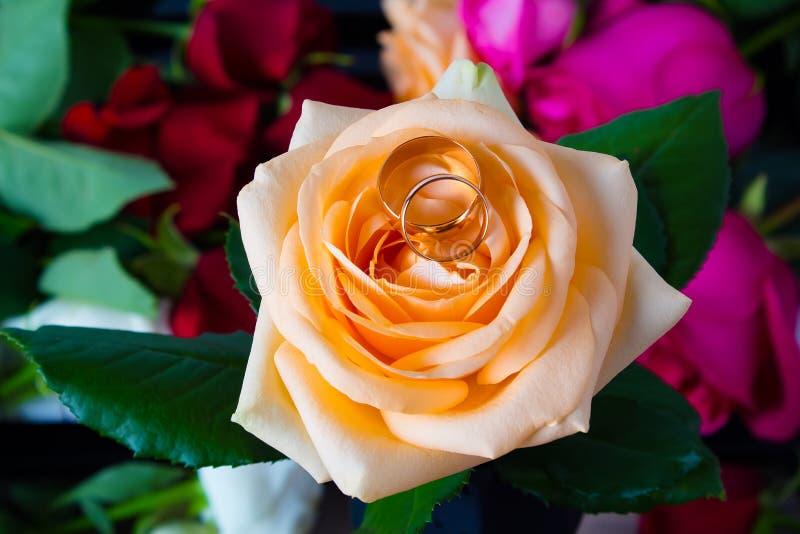 2 обручального кольца лежат на желтой розе на предпосылке цветков Кольца золота с цветками Подготовка для захвата или свадьбы стоковое изображение rf