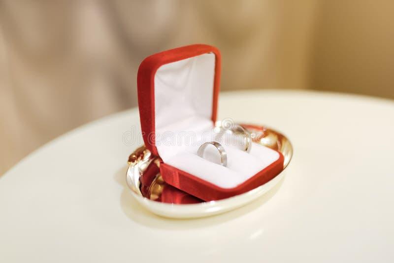 2 обручального кольца на белой подушке в красной коробке во время церемонии стоковые фото