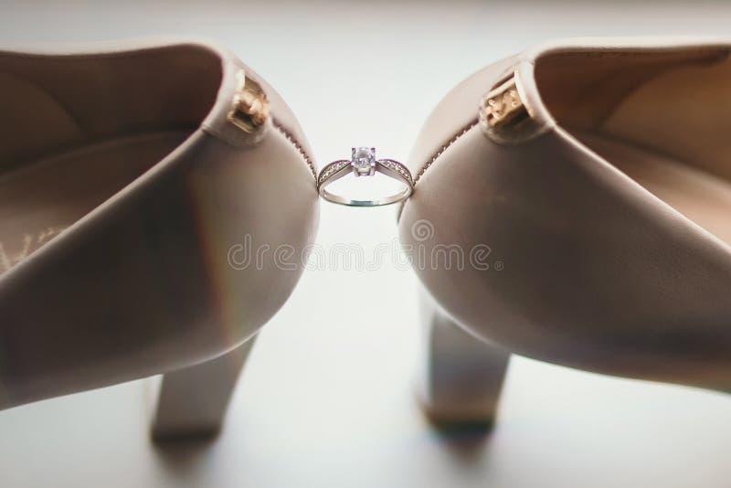 Обручальное кольцо между ботинками невест стоковое изображение rf