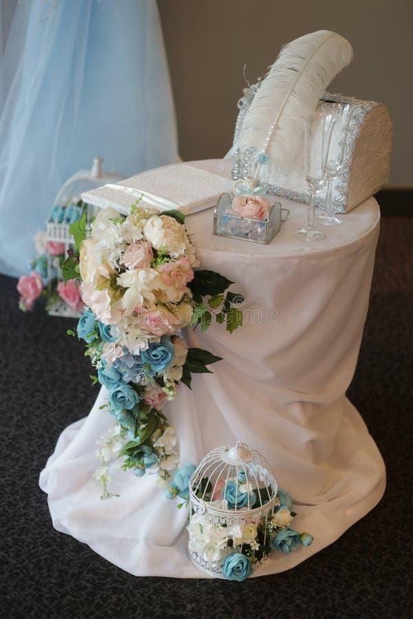 Обручальные кольца в стеклянной коробке с камнями, декоративной коробке, стеклах, ручке в чернильнице на таблице украшенной с роз стоковые фото