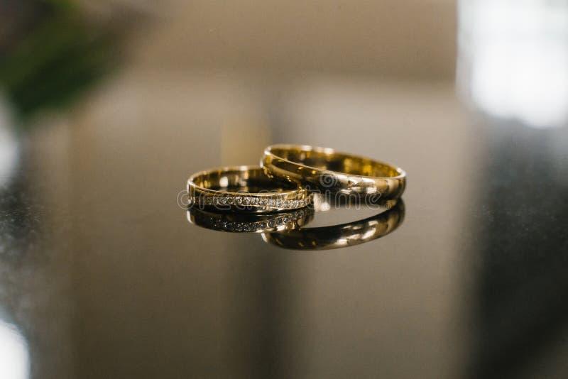 Обручальные кольца золота для жениха и невеста с камешками диамантов стоковые фото
