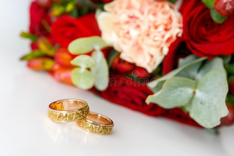 Обручальные кольца золота на белой предпосылке и букете невесты от роз стоковые фотографии rf