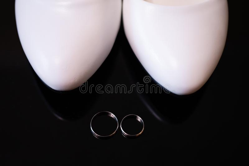 Обручальные кольца и белые bridal ботинки стоковая фотография rf