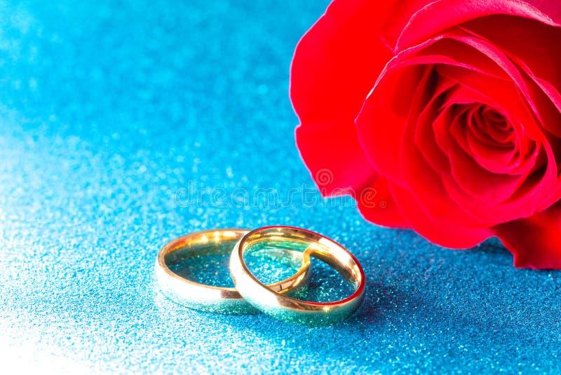 Обручальные кольца и красная роза на голубой предпосылке стоковые фотографии rf